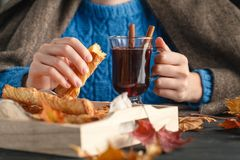 Woman holding mug of hot drink apple tea, mulled wine. Female hands with cup of seasonal hot drink. Homemade hot fruit tea. Stock Photo