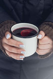 Woman holding mug of mulled wine in her hands outdoors Stock Photo