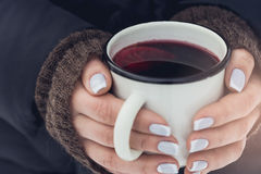Woman holding mug of mulled wine in her hands outdoors Stock Image