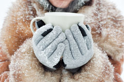 Woman holding a mug to get warm Stock Photography