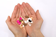 A woman holding multicoloured pills in hands Stock Photos