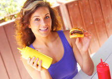 Woman Holding Mustard Sauce Bottle And Mini Burger. Portrait of beautiful young woman holding mustard sauce bottle and mini burger in both hands. Horizontal shot Royalty Free Stock Image