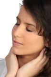 Woman holding neck Stock Image