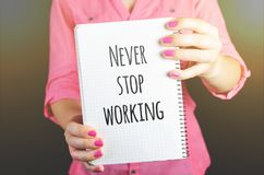 Woman Holding Never Stop Working Print Notebook Stock Photography
