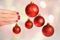 Woman holding New Year round balls ready to decorate tree. Close up of caucasian female hands with professional red manicure with glittering sparkles isolated on Stock Photo