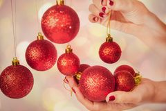 Woman holding New Year round balls ready to decorate tree. Close up of caucasian female hands with professional red manicure with glittering sparkles isolated on Royalty Free Stock Photography