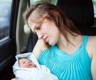 Woman holding newborn baby sitting in the car Stock Image