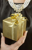 Woman holding nice gold gift. A hand royalty free stock images