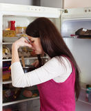 Woman holding nose because of bad smell from food. Brunnette woman holding her nose because of bad smell from food near refrigerator at home royalty free stock photos