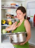 Woman holding nose near refrigerator Stock Photos