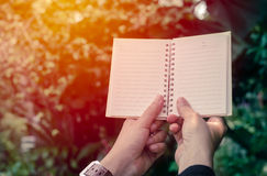 Woman holding notebook in sunrise. Background Stock Images