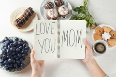 Woman holding notebook with words. `Love you mom` at table. Mother`s day breakfast Royalty Free Stock Photo