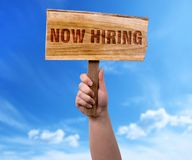 Now hiring wooden sign. A woman holding now hiring wooden sign on blue sky background stock images