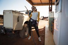 Woman holding a nozzle at petrol pump station. On a sunny day Stock Photo