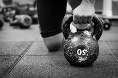 Woman holding old and rusty kettle bell on to the gym floor. stock images