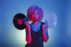Woman holding oldies music vinyls in colorful neon lights. African american woman holding a pair of music vinyls in colorful neon lights royalty free stock photography