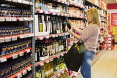 Woman Holding Olive Oil Bottle In Supermarket Stock Images