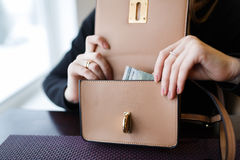 Woman holding a one hundred dollar bill. Young woman pulls from her purse a one hundred dollar bill Stock Photography