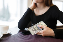Woman holding a one hundred dollar bill. Young woman holding a one hundred dollar bill sitting in a cafe waiting for the waiter Royalty Free Stock Photos
