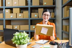 Woman holding online shopping order parcel. Confident smiling office worker women holding online shopping order parcel and wearing earphone sitting in warehouse Royalty Free Stock Photos