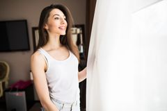 Woman holding open curtains while looking out of the window in the morning Royalty Free Stock Image