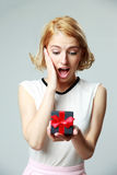Woman holding an open jewelery gift box. Surprised beautiful young woman holding an open jewelery gift box Royalty Free Stock Image