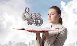 Woman holding open notebook with mechanism. Woman holding open notebook with flying abstract mechanism with cogwheels. Construction and manufacturing concept royalty free stock images