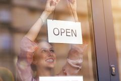 Woman holding open sign in cafe royalty free stock image