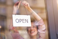Woman holding open sign in cafe royalty free stock photos