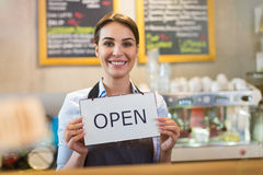 Woman holding open sign in cafe Stock Photo