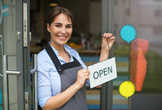 Woman holding open sign in cafe Royalty Free Stock Images