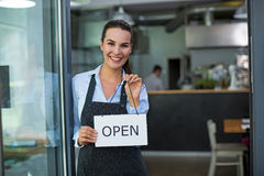 Woman holding open sign in cafe. Young woman holding open sign in cafe Stock Photography