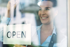 Woman holding open sign in cafe Stock Images