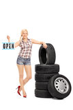 Woman holding an open sign next to a stack of tires Stock Image