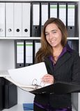 Woman is holding an opened file in front of a shelf Royalty Free Stock Images