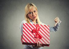 Woman holding, opening gift box, displeased with what she received Stock Photo