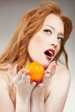 Woman holding an orange Royalty Free Stock Photos