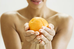 A woman holding an orange in both hands Royalty Free Stock Photos
