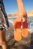 Woman holding orange flops on the shoreline Royalty Free Stock Images