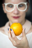 Woman holding an orange in her hand Stock Photo