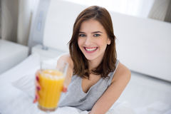 Woman holding orange juice on the bed Stock Images