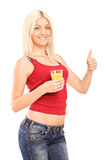 Woman holding an orange juice and giving thumb up Royalty Free Stock Photography