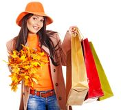 Woman holding orange leaves. Woman wearing autumn overcoat and hat holding shopping bag royalty free stock photos