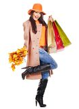 Woman holding orange leaves. Woman wearing autumn overcoat and hat holding shopping bag royalty free stock photography