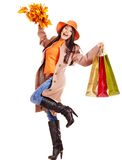 Woman holding orange leaves. Woman wearing autumn overcoat and hat holding shopping bag stock image