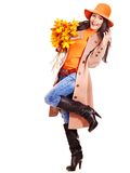 Woman holding orange leaves. Woman wearing overcoat holding orange leaves stock photo