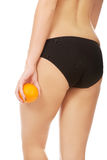 Woman holding orange next to buttocks. Royalty Free Stock Images