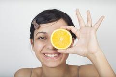 Woman holding orange over eyes Royalty Free Stock Photos