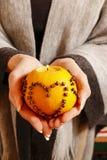Woman holding orange pomander ball Royalty Free Stock Photos
