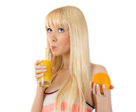 Woman holding orange while sipping glass of juice Stock Photos